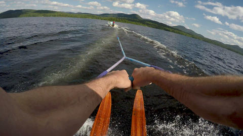 POV of a healthy fit man water skiing on vintage wooden water skis on a pristine Footage