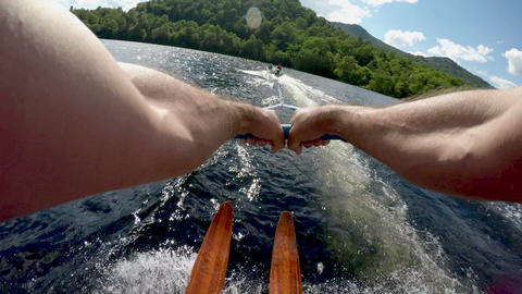 POV of young man water skiing on vintage wooden water skis a clear blue mountain 画像