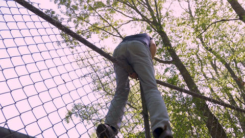 Low angle of a man climbing over a chain link fence trespassing in private Live Action