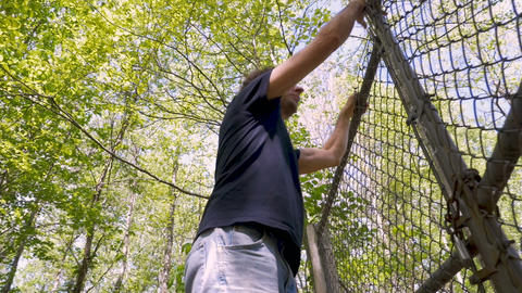Low angle of a man carefully climbing over a chainlink fence breaking into Footage