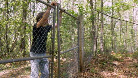 A man in his 30s or 40s being chased quickly climbs over a chain link fence Footage