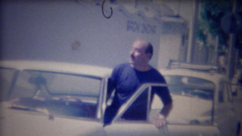 1963: Balding Italian chauffeur man enters classic white Fiat car Live Action