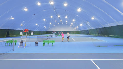 Two people comes to play tennis at the indoors court Live Action