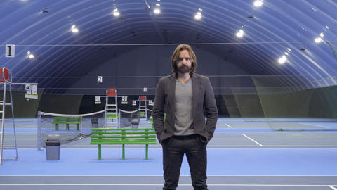 Man stands in the dark and lamps illuminates the territory of the tennis court Footage
