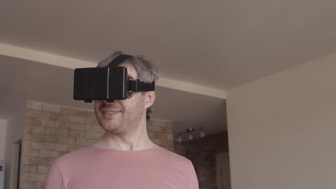 Grey haired man having fun using his mobile phone virtual reality headset at Footage