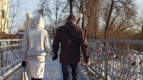 Couple walking holding hands on a small bridge near catherdral. 4K steadicam Footage