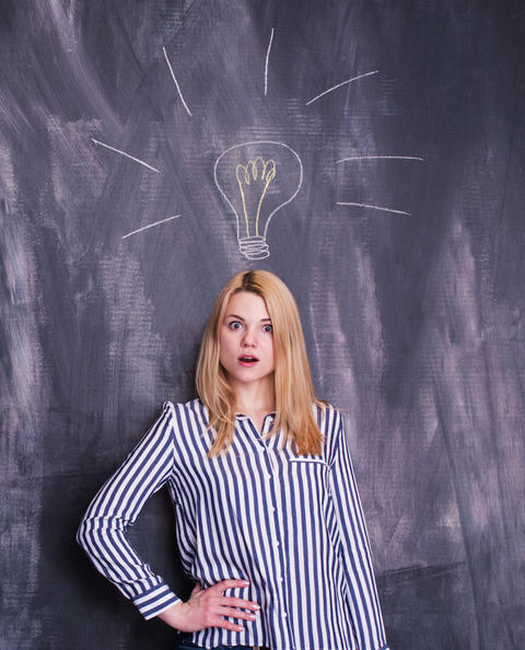 Girl in front of chalkboard with light bulb drawn above her head Photo