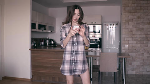 Pretty young woman in plaid shirt dancing at home. Steadicam 4K shot Footage