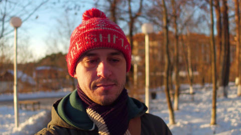 Pensive man in red hat walking in winter park Footage