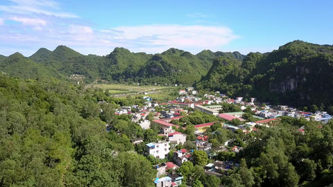 Aerial View Small Modern City among Green Forestry Hills Live Action