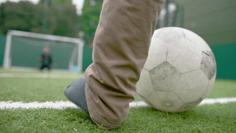 Close up on child kicking football at goal Footage