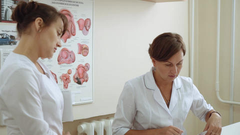 A female doctor shows a medical chart to a sick doctor Footage