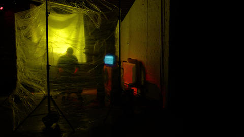 A man slaps a man repeatedly behind cling film under yellow lighting Footage
