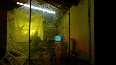 Two obscured figures in a sinister yellow and red lit room Live Action