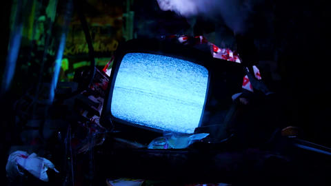 Spooky zoom out of TV in junk yard Live Action