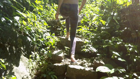 Backside View Girl Goes up Stone Steps between Plants Footage