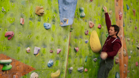 Professional boulder climbing on a steep wall and breaks down. The climbing wall Live Action