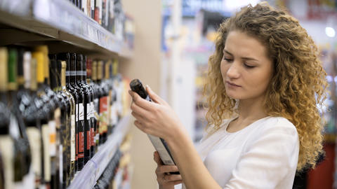 Woman Chooses Wine In The Supermarket Footage
