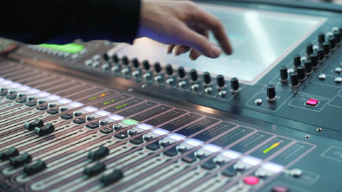 Audio engineer working on a professional console, moving faders, mixing music Footage