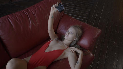 Sexy young woman lying on sofa and taking selfie Footage