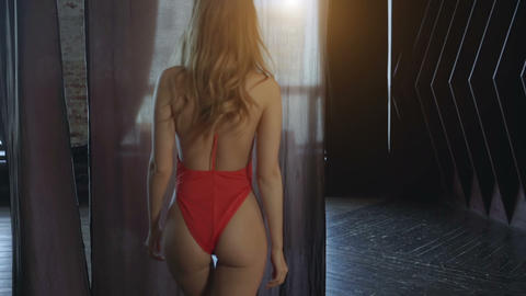 Sexy girl in red swimsuit goes towards the couch Footage