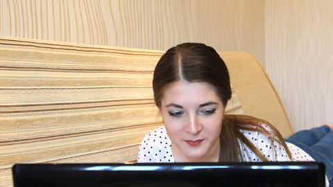 Face of girl using a laptop lying on the couch 2 Footage