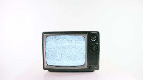 An old fashioned television turning on and playing static on a white background Live Action