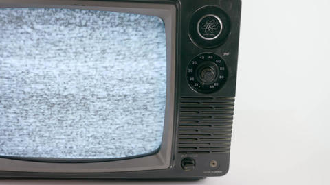 Close up shot of a vintage television turning on and playing static Live Action