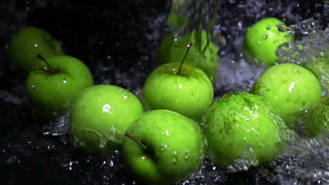 Spilling water over green apples Footage