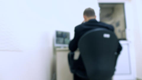 Blurred security guard at surveillance monitor Footage