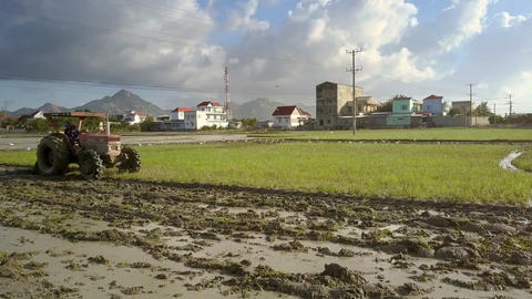 Close Tractor Plows Ground for Future Rice Field by Village 画像