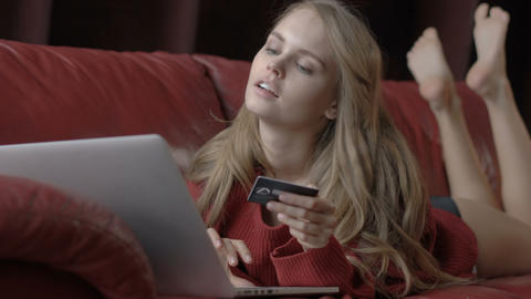 Beautiful smiling blonde woman leaning on red sofa while using laptop and credit Footage