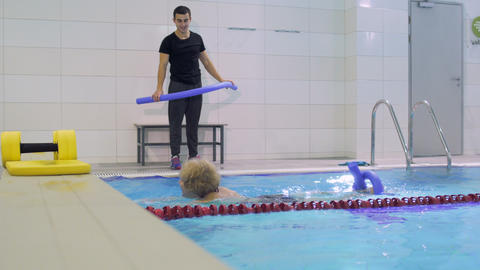 Coach show swimming exercise with noodle to elderly woman Footage