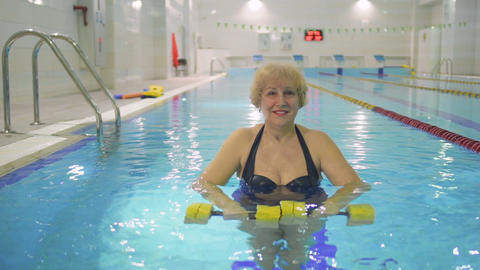 Attractive smiling senior woman with dumbbells in swimming pool Footage