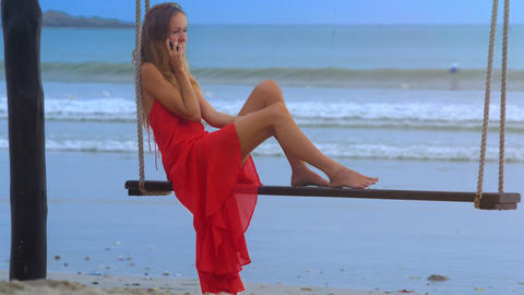 Girl Sits on Swing Touches Wet Sand with Bare Foot Live影片