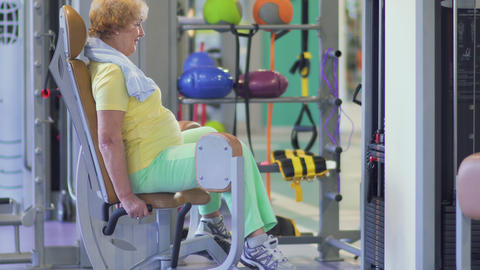 Cute granny trains her legs in the gym on training apparatus Live Action