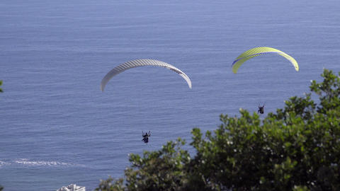 Two paragliders drift in the wind near Cape Town Footage