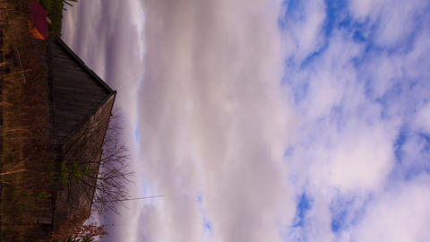 Vertical video. Clouds sweep over the barn. Time Lapse Footage