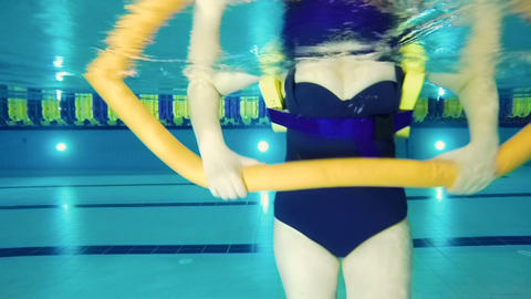 Underwater shooting - senior woman make exercise with noodle in swimming pool Footage