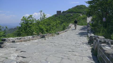 Western male tourist enjoys walking along Great Wall Bild