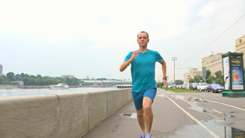 Sportsman in blue uniform running at camera on river embankment after rain Live Action
