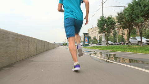 Athletic man in blue uniform running from camera on river embankment after rain Live Action