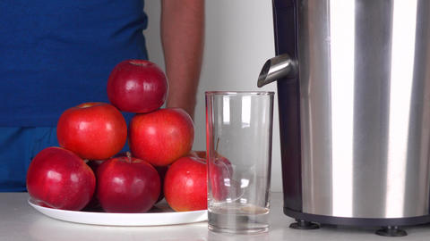 Man making red apple juice with shiny juicer. 4K close up shot Footage