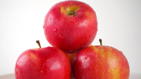 Red apples and dripping water, light background. 4K ProRes close up dolly shot Footage