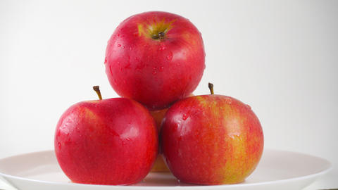 Red apples on plate and dripping water against white background. 4K ProRes dolly Footage
