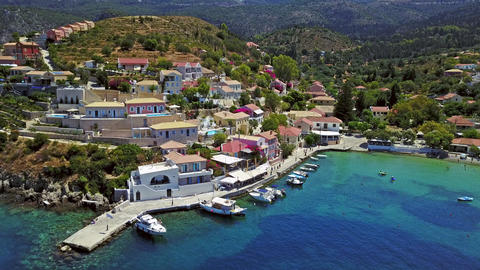 Aerial shot of a town in a bay with boats and people on the beach on Kefalonia, Footage