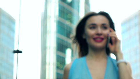 Happy brunette girl in blue dress speaking on her mobile phone on the street Footage