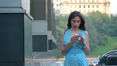 Thoughtful brunette girl in blue dress touching her phone on the street, super Footage