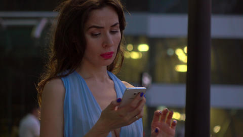 Brunette girl in blue dress talking on her smartphone on the street at night. 4K Footage