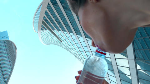 Beautiful girl drinking water from the bottle against skysrapers, 4K close up Footage